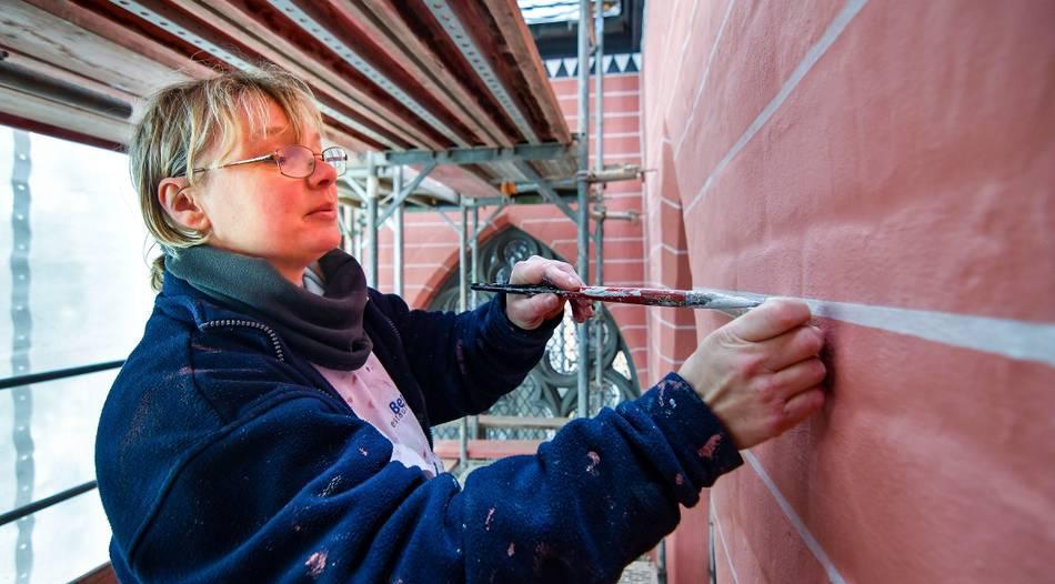 Malerin Martina Wietfeld arbeitet nicht das erste Mal an der Propsteikirche. Bereits vor 30 Jahren war sie bei der letzten Fassadensanierung dabei. Foto: Norbert Prümen